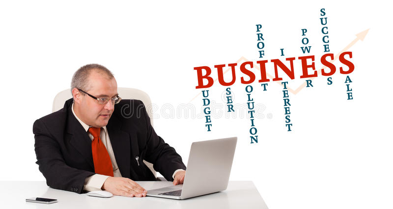 Bisinessman sitting at desk and looking laptop with business word cloud. Isolated on white royalty free stock image