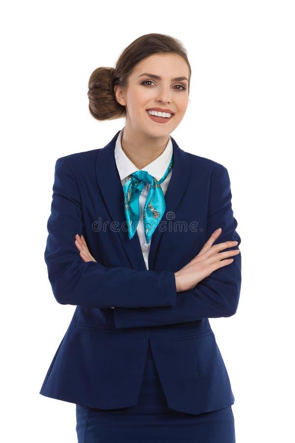 Bisinesswoman de sorriso no terno azul com os braços cruzados fotografia de stock
