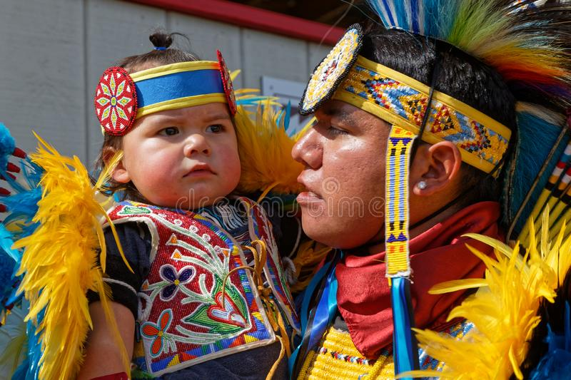 Baby and father at the 49th annual United Tribes Pow Wow. BISMARK, NORTH DAKOTA, September 8, 2018 : A family at the 49th annual United Tribes Pow Wow, one large royalty free stock photos