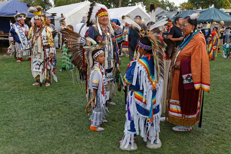 A family gathers outside at the 49th annual United Tribes Pow Wow, one large outdoor event that gathers. BISMARK, NORTH DAKOTA, September 8, 2018 : A family at stock photography