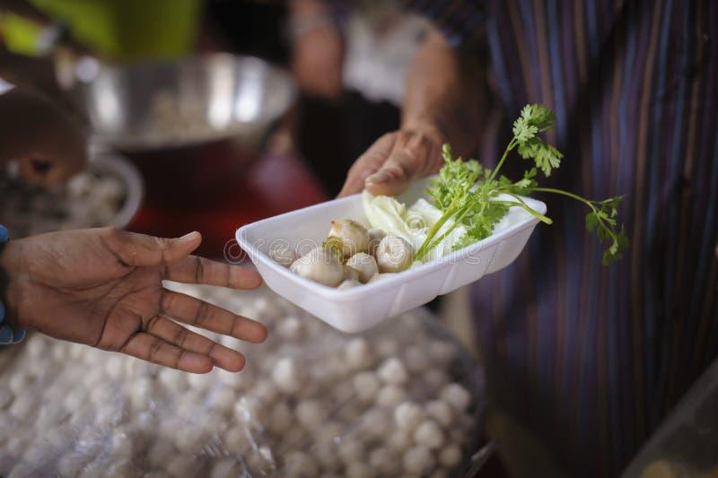 Bisogni dell'alimento del povero nell'aiuto della società con donazione dell'alimento: Il barbone prende l'alimento della carità  fotografie stock libere da diritti