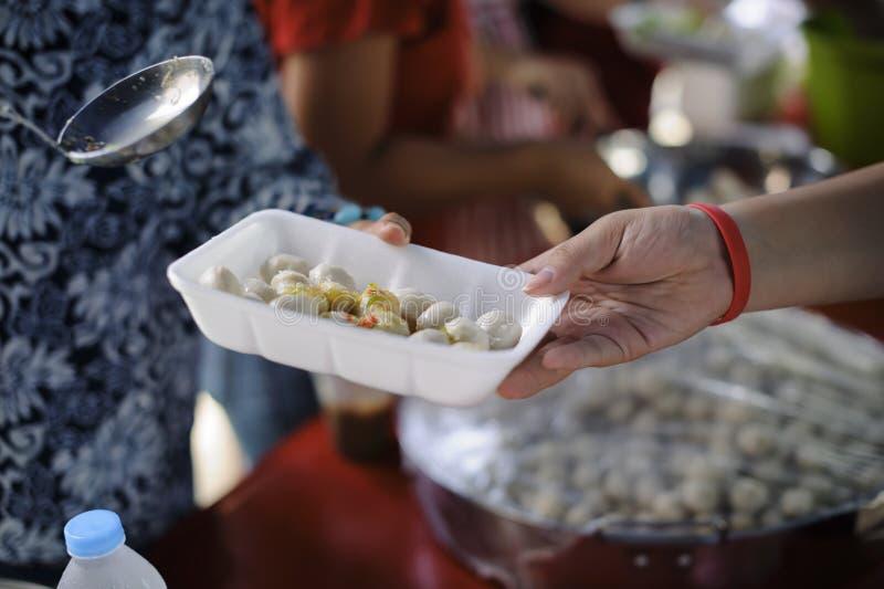 Bisogni dell'alimento del povero nell'aiuto della società con donazione dell'alimento: Il barbone prende l'alimento della carità  immagine stock