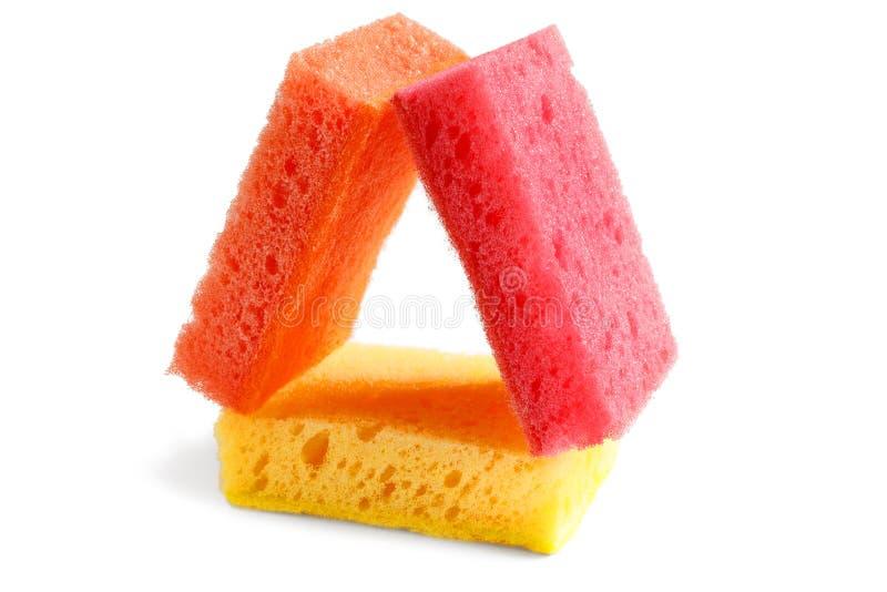 Bisogni domestici Le spugne arancio e rosse sono su giallo I colori allegri migliorano l'umore, rendono il lavoro domestico facil fotografie stock libere da diritti