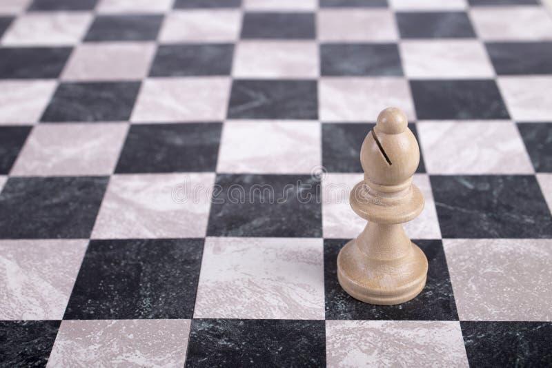 Bispo de madeira branco no tabuleiro de xadrez imagem de stock