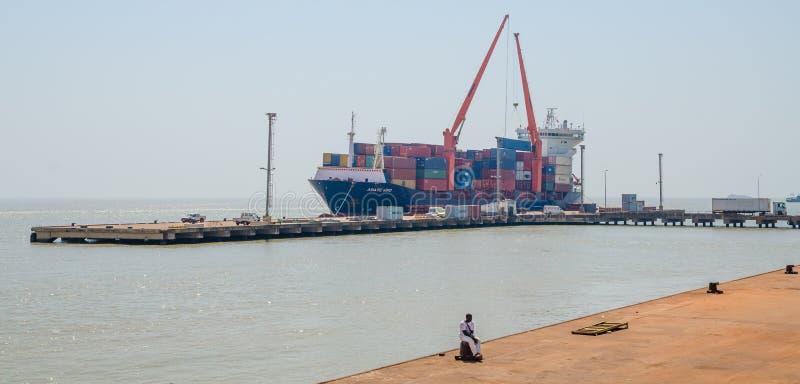 Bissau Guinea Bissau - December 06, 2013: Behållareskepp som lastar av på liten port av Bissau arkivfoto