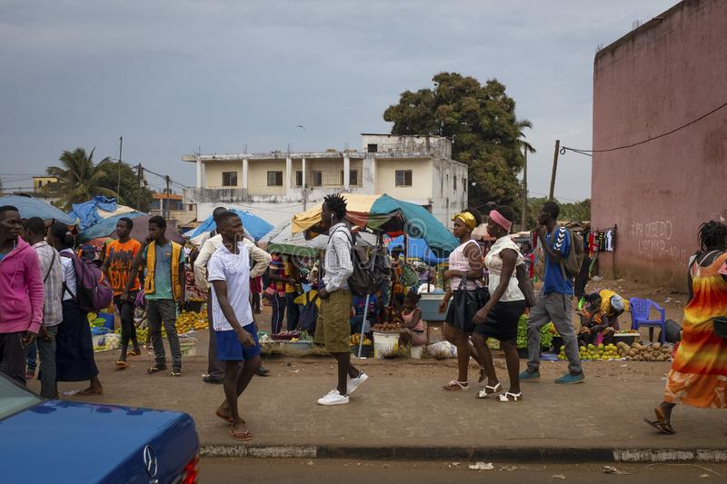 Street scene in the city of Bissau with people walking on a sidewalk near a street market, in Guinea-Bissau. Bissau, Republic of Guinea-Bissau - February 6, 2018 royalty free stock images