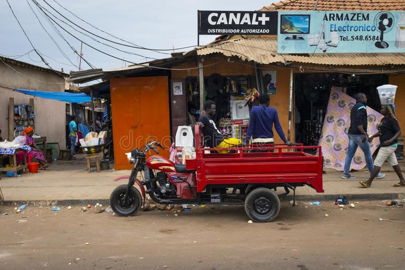 Street scene in the city of Bissau with people walking on a sidewalk and stores near the Bandim Market, in Guinea-Bissau. Bissau, Republic of Guinea-Bissau royalty free stock photography
