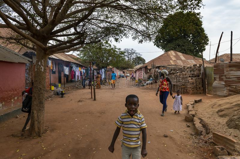 Street scene at the Missira neighbourhood, with people on a dirt street, in the city of Bissau. Bissau, Republic of Guinea-Bissau - February 6, 2018: Street stock photography