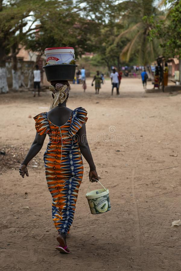 A woman walking along a dirt street carrying a bucket on her head, in the city of Bissau, in Guinea-Bissau. Bissau, Republic of Guinea-Bissau - February 8, 2018 stock photography