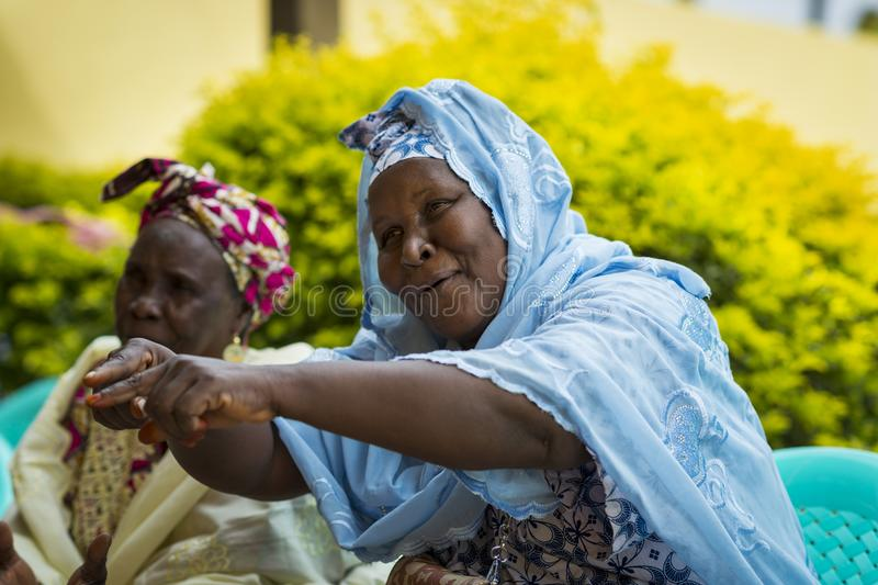 Group of women singing traditional songs at a community meeting in the city of Bissau, Guinea-Bissau. Bissau, Republic of Guinea-Bissau - January 31, 2018: Group stock image