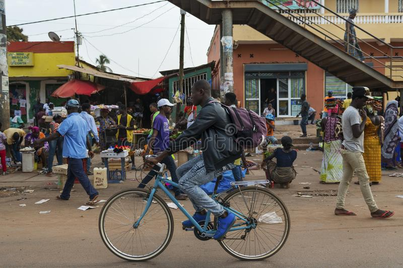 Street scene in the city of Bissau with a man riding his bicycle in front of the Bandim Market, in Guinea-Bissau. Bissau, Republic of Guinea-Bissau - January 28 royalty free stock image