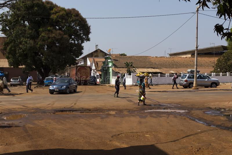 Street scene in the city of Bissau with people crossing the Amilcar Cabral Avenue, in Guinea-Bissau. Bissau, Republic of Guinea-Bissau - January 30, 2018 royalty free stock photography
