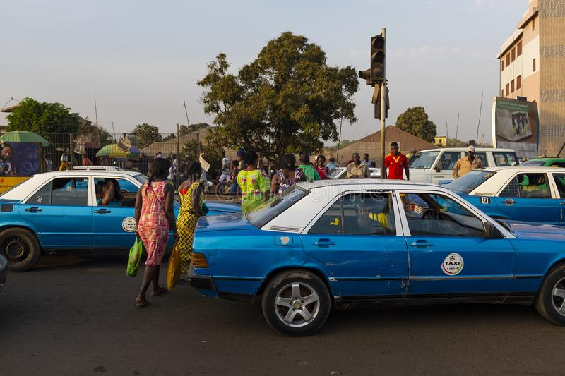 Street scene in the city of Bissau with people crossing a road between the cars, near the Bandim Market, in Guinea-Bissau. Bissau, Republic of Guinea-Bissau stock photos