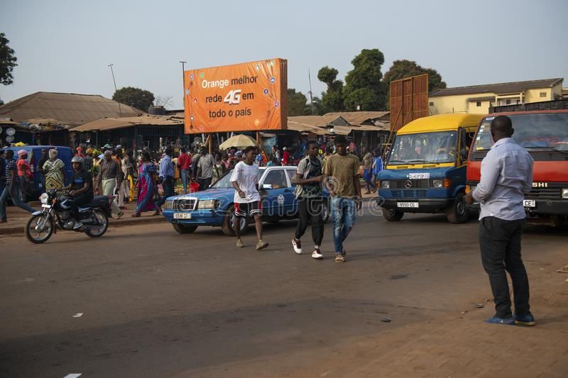 Street scene in the city of Bissau with people walking crossing a street near the Bandim Market, in Guinea-Bissau. Bissau, Republic of Guinea-Bissau - January 31 royalty free stock photos