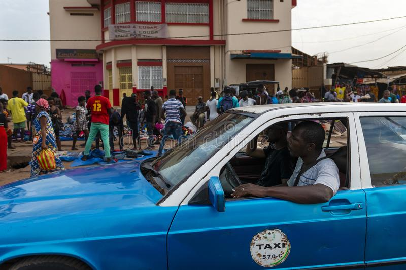 Street scene in the city of Bissau with a taxi and people at the Bandim Market, in Guinea-Bissau. Bissau, Republic of Guinea-Bissau - January 28, 2018: Street royalty free stock photo
