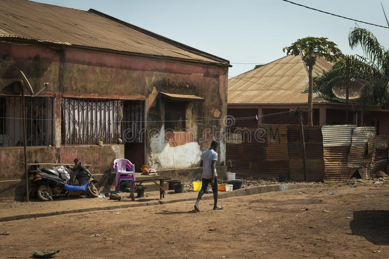 Street scene in the city of Bissau with a young man walking along a dirt road in a slum, in Guinea-Bissau. Bissau, Republic of Guinea-Bissau - January 29, 2018 royalty free stock images