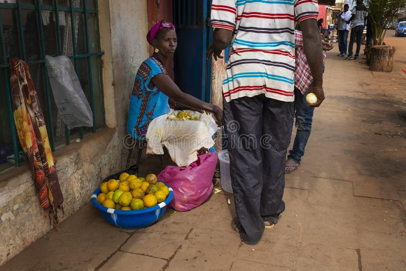 Street scene in the city of Bissau with a woman selling oranges, in Guinea-Bissau, West Africa. Bissau, Republic of Guinea-Bissau - February 5, 2018: Street royalty free stock images