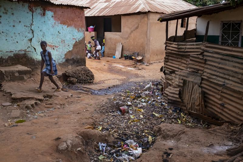 Young girl walking on a dirt street in a slum with an open air sewer, at the city of Bissau. Bissau, Republic of Guinea-Bissau - February 6, 2018: Young girl stock photos