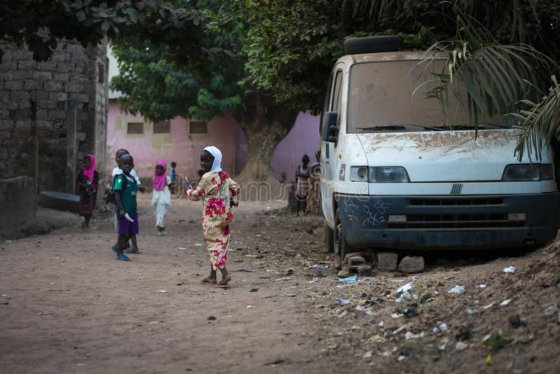 Group of children playing in dirt street at the Cupelon de Baixo neighborhood in the city of Bissau. Bissau, Republic of Guinea-Bissau - January 31, 2018: Group stock photos