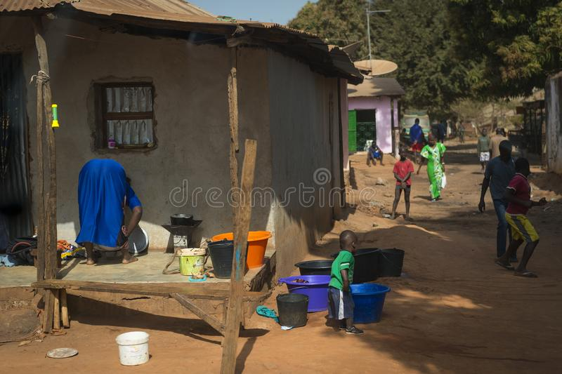 People in a street of a slum in the city of Bissau, in Guinea Bissau. Bissau, Republic of Guinea-Bissau - January 29, 2018: People in a street of a slum in the stock photos