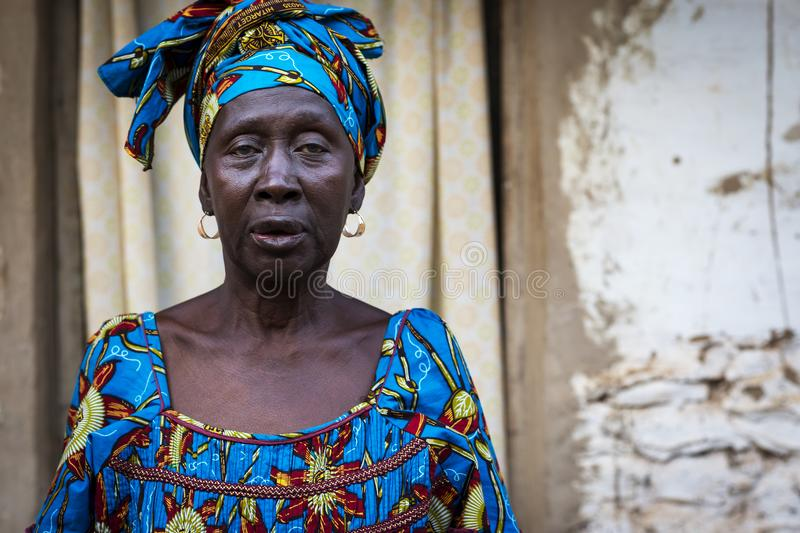 Portrait of an African woman wearing a colorful dress in a slum of the city of Bissau, in Guinea-Bissau. Bissau, Republic of Guinea-Bissau - January 29, 2018 stock image