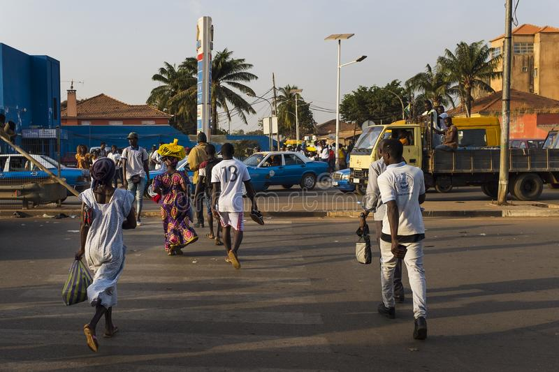 Street scene in the city of Bissau with people crossing a road in a crosswalk, near the Bandim Market, in Guinea-Bissau. Bissau, Republic of Guinea-Bissau royalty free stock photos