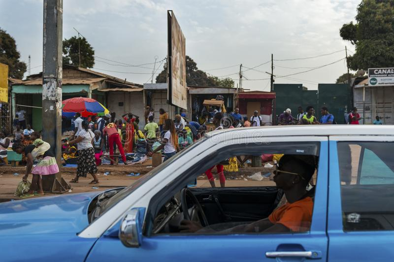 Street scene in the city of Bissau with a taxi and people at the Bandim Market, in Guinea-Bissau. Bissau, Republic of Guinea-Bissau - January 28, 2018: Street royalty free stock image