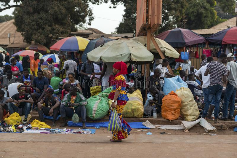 Street scene in the city of Bissau with woman wearing a colorful dress walking in a sidewalk and the Bandim Market on the backgrou. Bissau, Republic of Guinea stock photography