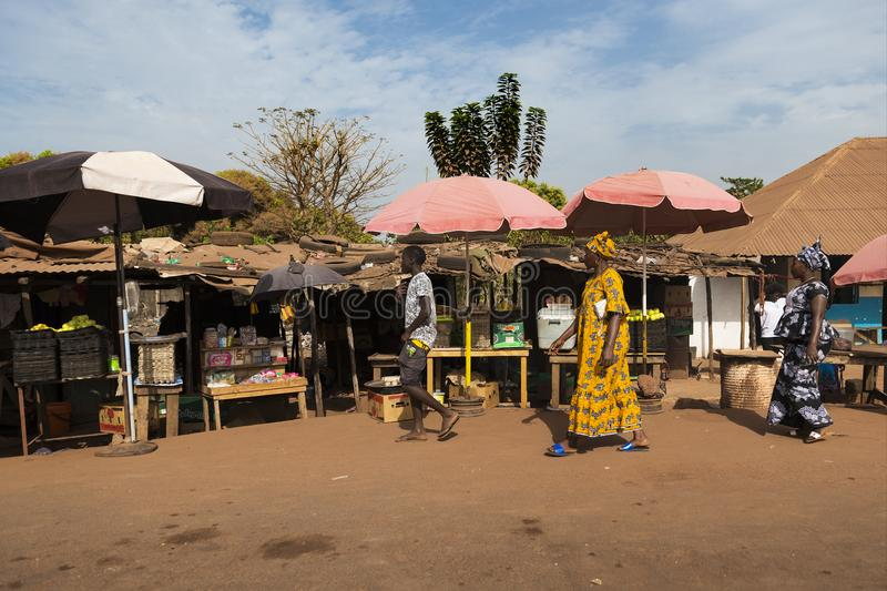 Street scene in the city of Bissau with women wearing colorful dresses in a street market, in Guinea-Bissau. Bissau, Republic of Guinea-Bissau - January 28, 2018 stock image