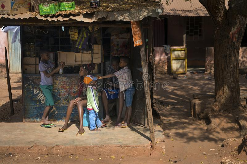 Young family in front of their small store in a slum of the city of Bissau. Bissau, Republic of Guinea-Bissau - January 29, 2018: Young family in front of their royalty free stock photography