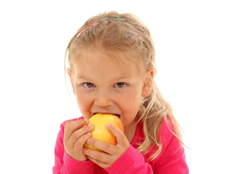 Bisse des kleinen Mädchens in einem Apfel lizenzfreie stockbilder