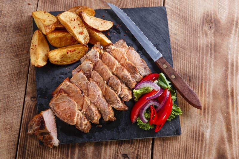 Bistecca affettata della carne di maiale con le patate immagini stock