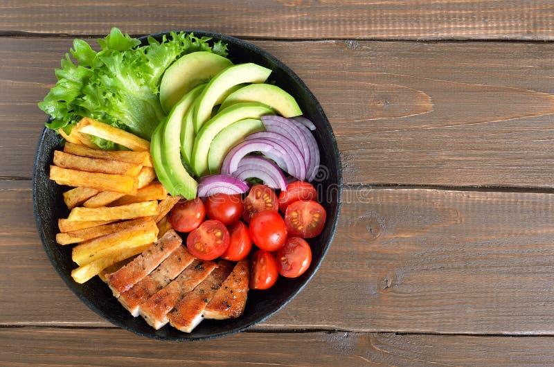 Bistecca affettata grigliata della carne di maiale con le patate, i pomodori e gli avocado immagini stock libere da diritti