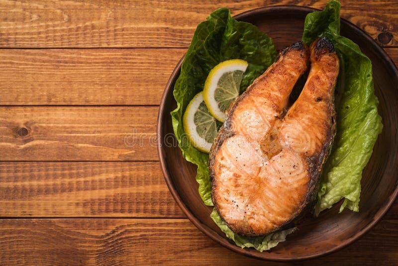 Bistecca al forno della trota in terraglie con insalata e le fette di limone fotografie stock libere da diritti