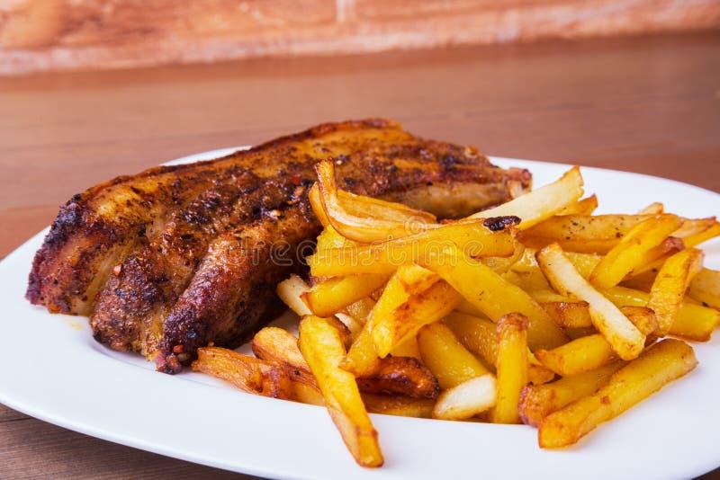 Bistecca arrostita affettata di Striploin del barbecue delle costole di carne di maiale con la salsa e la patata di chimichurri l fotografia stock libera da diritti