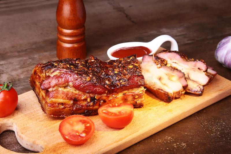 Bistecca arrostita affettata di Striploin del barbecue delle costole di carne di maiale con la salsa ed i pomodori di chimichurri fotografie stock libere da diritti