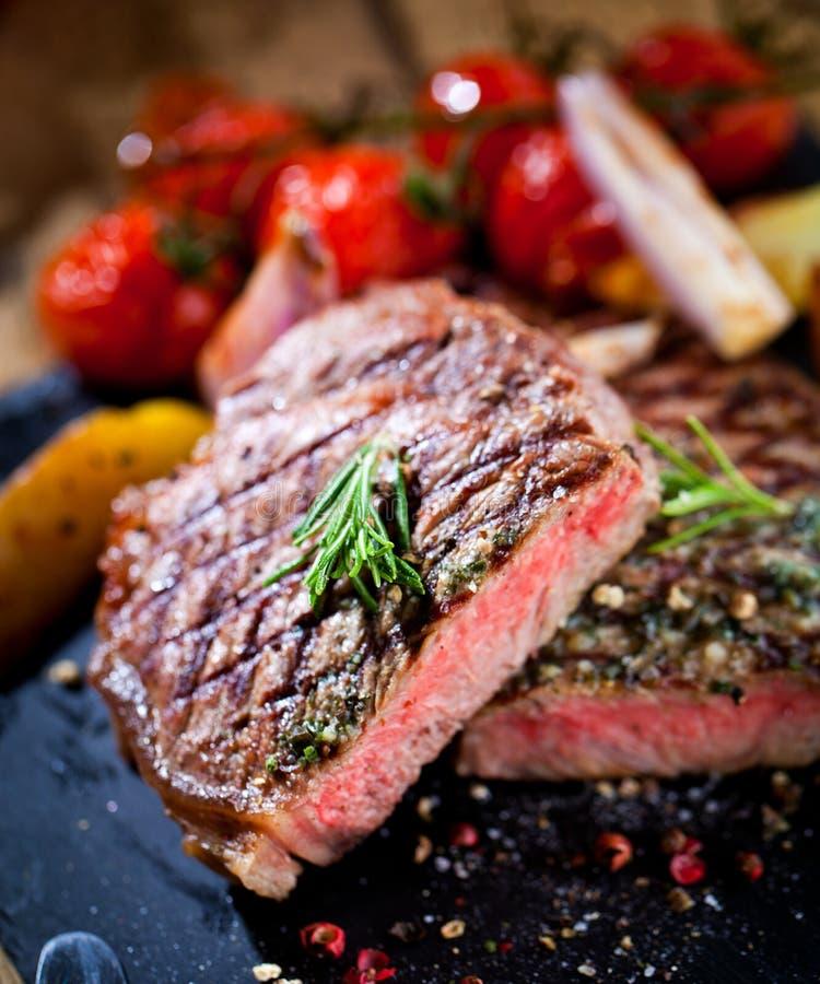 Bistecca arrostita affettata Striploin del barbecue della carne con il coltello e forcella che scolpisce insieme sull'ardesia di  fotografia stock