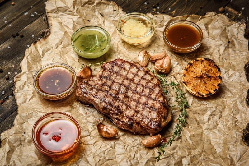 Bistecca arrostita con differenti salse, su pergamena Vista superiore verticale immagine stock libera da diritti