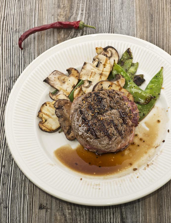 Bistecca arrostita con i funghi e le taccole immagine stock libera da diritti