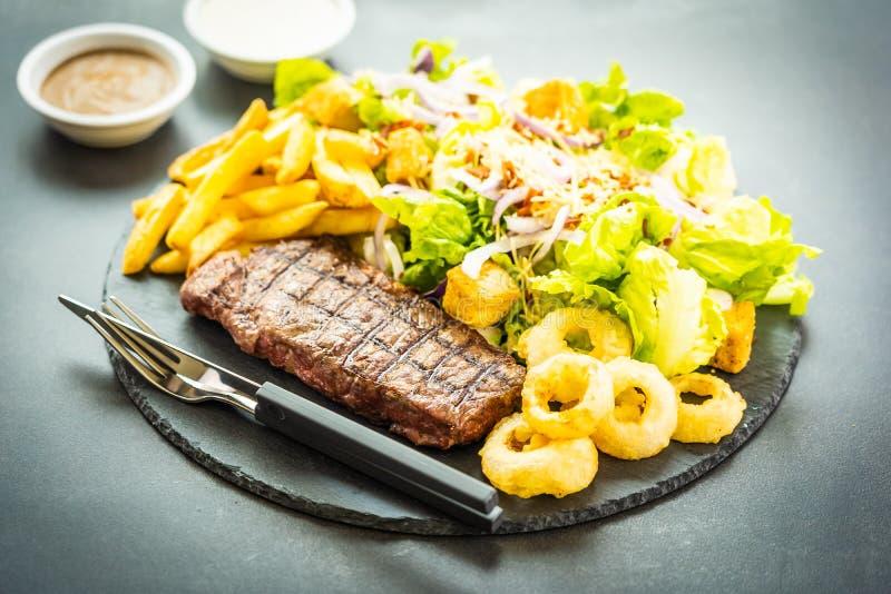 Bistecca arrostita della carne del manzo con l'anello di cipolla delle patate fritte con salsa e la verdura fresca fotografia stock libera da diritti