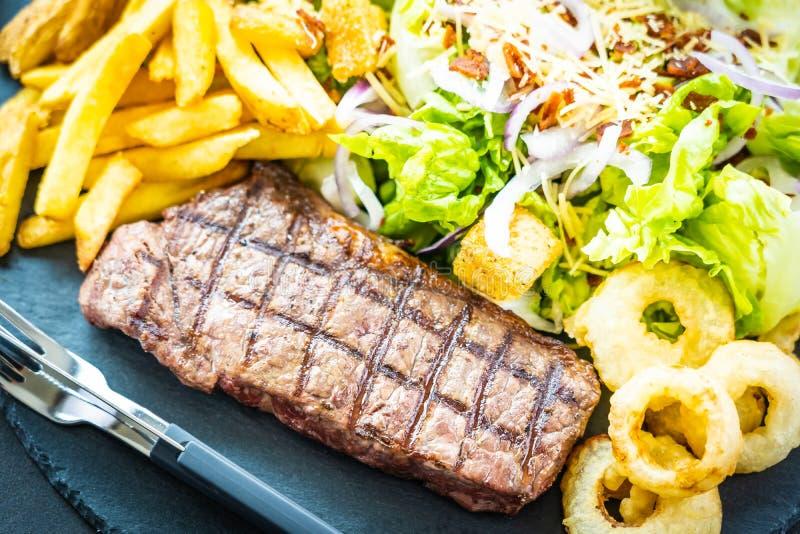 Bistecca arrostita della carne del manzo con l'anello di cipolla delle patate fritte con salsa e la verdura fresca fotografia stock