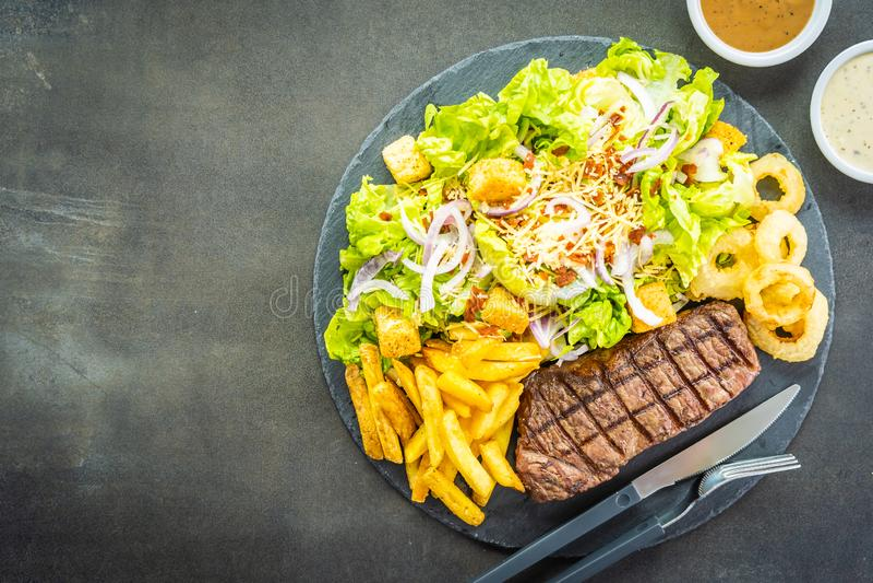 Bistecca arrostita della carne del manzo con l'anello di cipolla delle patate fritte con salsa e la verdura fresca immagini stock