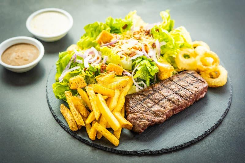 Bistecca arrostita della carne del manzo con l'anello di cipolla delle patate fritte con salsa e la verdura fresca immagine stock