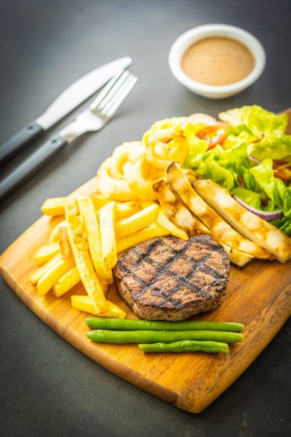 Bistecca arrostita della carne del manzo con la salsa delle patate fritte e la verdura fresca fotografie stock