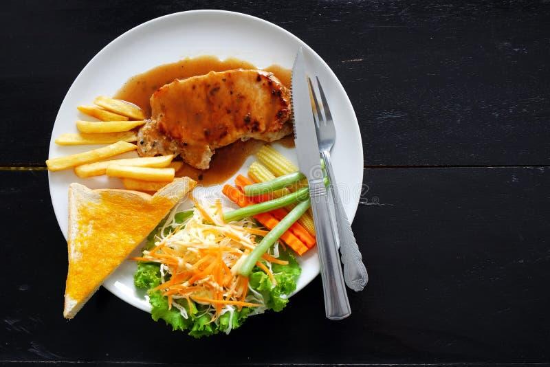 Bistecca arrostita della carne di maiale con pane all'aglio ed insalata immagini stock