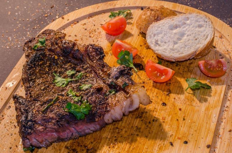 Bistecca arrostita della carne di maiale con pane francese e prezzemolo sulla cima fotografia stock