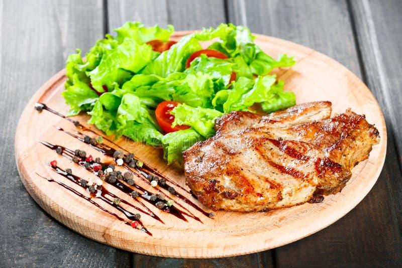 Bistecca arrostita di braciola di maiale con l'insalata, i pomodori e la salsa della verdura fresca sul tagliere di legno Piatti  immagini stock libere da diritti