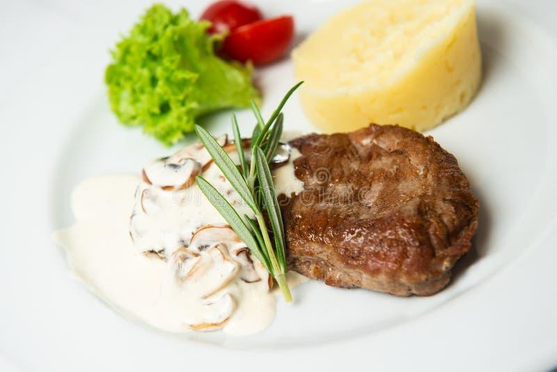 Bistecca arrostita fresca succosa con i funghi prataioli e le purè di patate Decorato con insalata, i pomodori ciliegia ed i rosm fotografia stock