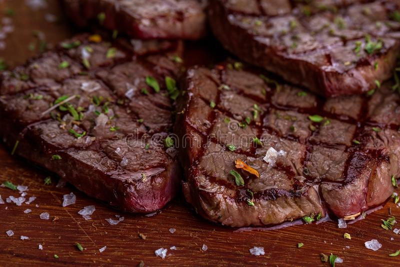 Bistecca arrostita liced calda di Striploin del barbecue del manzo sul tagliere su fondo di legno scuro immagine stock