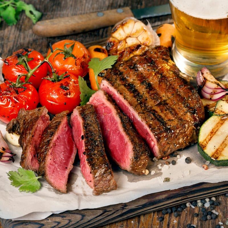 Bistecca arrostita rara affettata con le verdure arrostite e la birra chiara fotografia stock libera da diritti